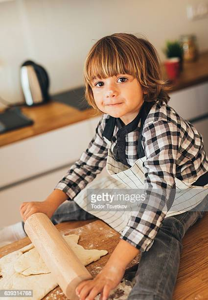 Little boy rolling out dough