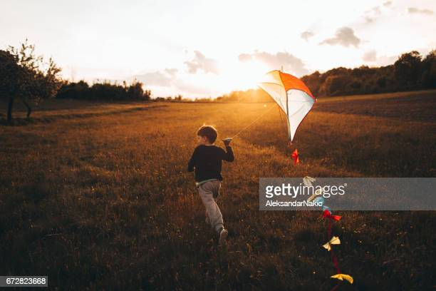 Little boy running a kite