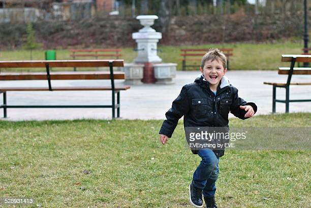 Little boy running happily in the park