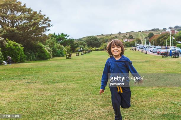 little boy running in a grass field - sports track stock pictures, royalty-free photos & images