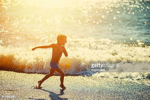 little boy running in front of sea waves - só um menino - fotografias e filmes do acervo