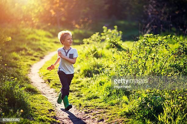 little boy running in spring - 6 7 jahre stock-fotos und bilder