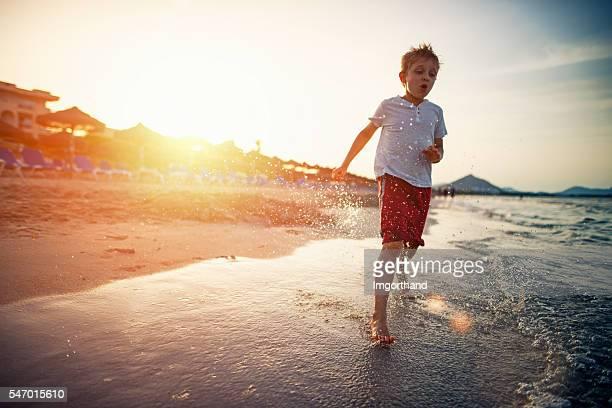 Little boy running on beach on sunset
