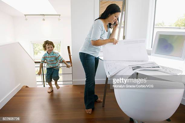 Little boy running through house while mother is working