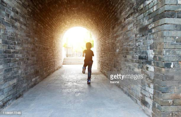 little boy running through the tunnel - escaping stock pictures, royalty-free photos & images
