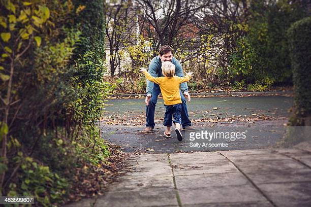 little boy running to his father - son stock pictures, royalty-free photos & images