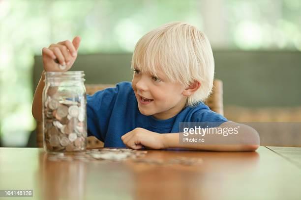 Little Boy Saving Coins In A Glass Jar
