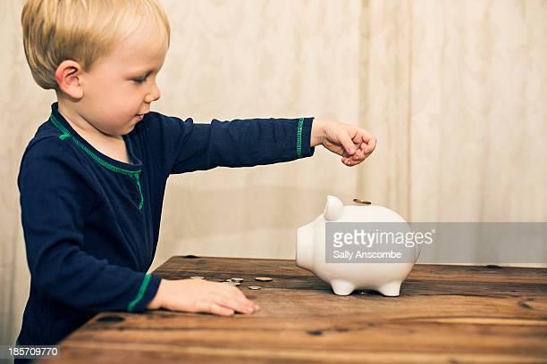 Little boy saving his money in a piggy bank