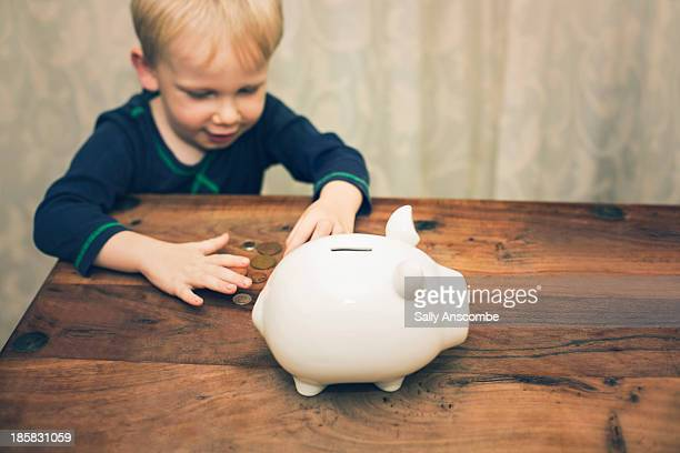 little boy saving money in a piggybank - putting stock pictures, royalty-free photos & images