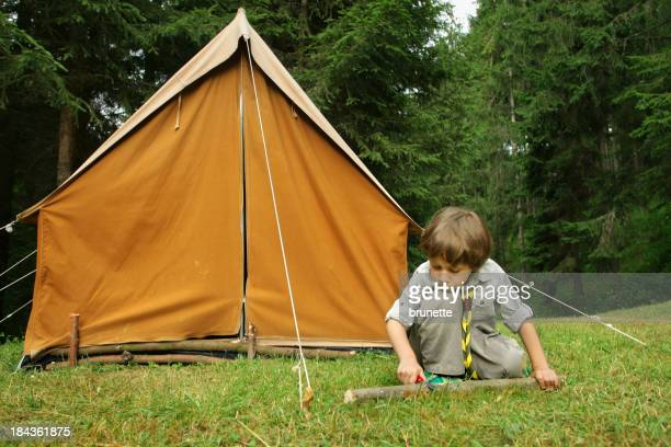 Little Boy Scout building a orange tent