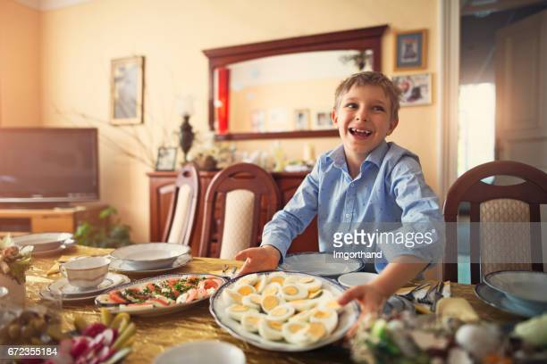 Little boy setting the table for traditional easter breakfast