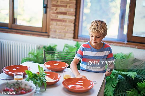 Little boy setting up table for family lunch.