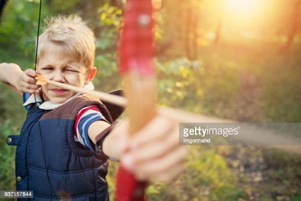 Little boy shooting bow in forest