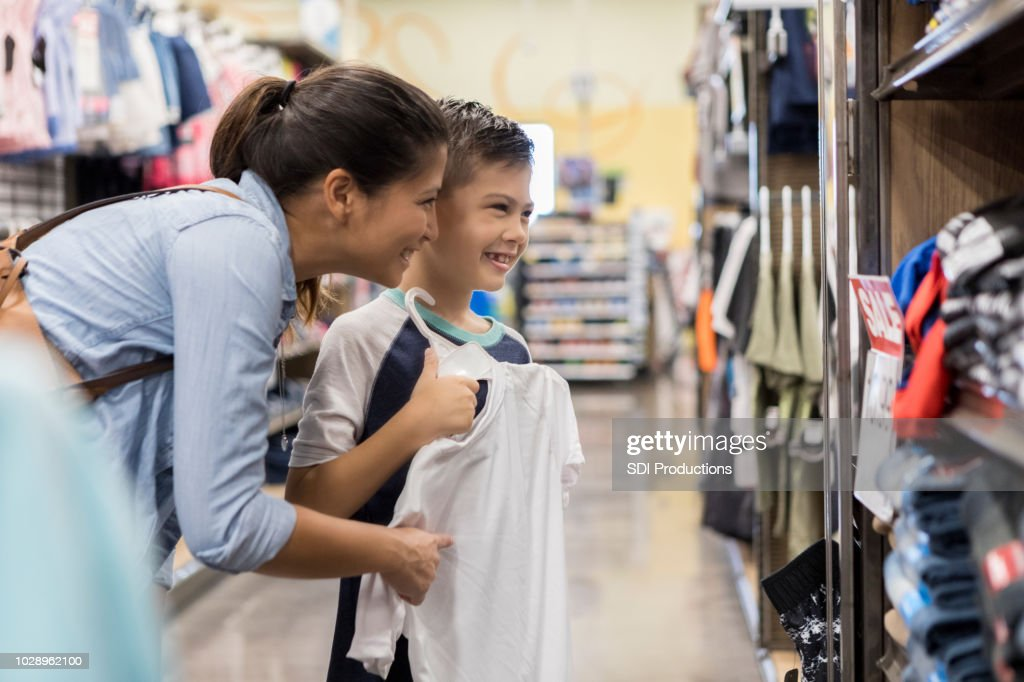 Little boy shops with his mid adult mom : Stock Photo