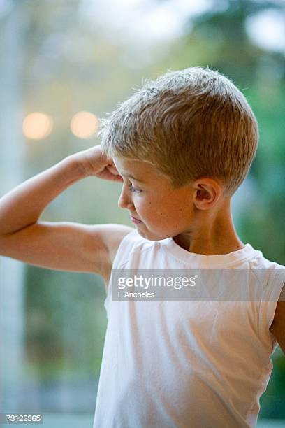 A little boy showing his muscles.