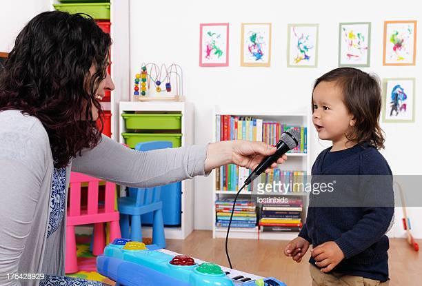 Petit garçon chanter tandis que son Carer prises Microphone