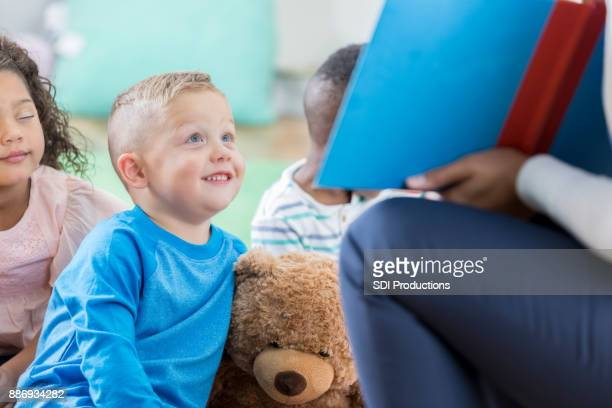 Little boy sits with teddy bear during preschool story time