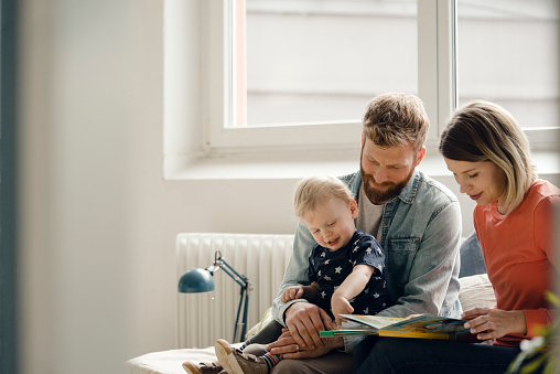 Little boy sittiing on father's lap, mother reading out children's book - gettyimageskorea