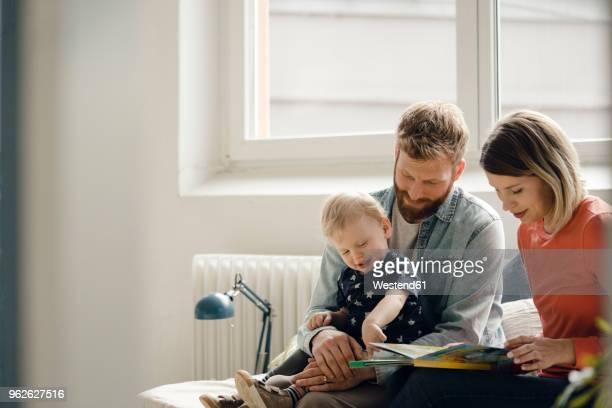 little boy sittiing on father's lap, mother reading out children's book - behaglich stock-fotos und bilder