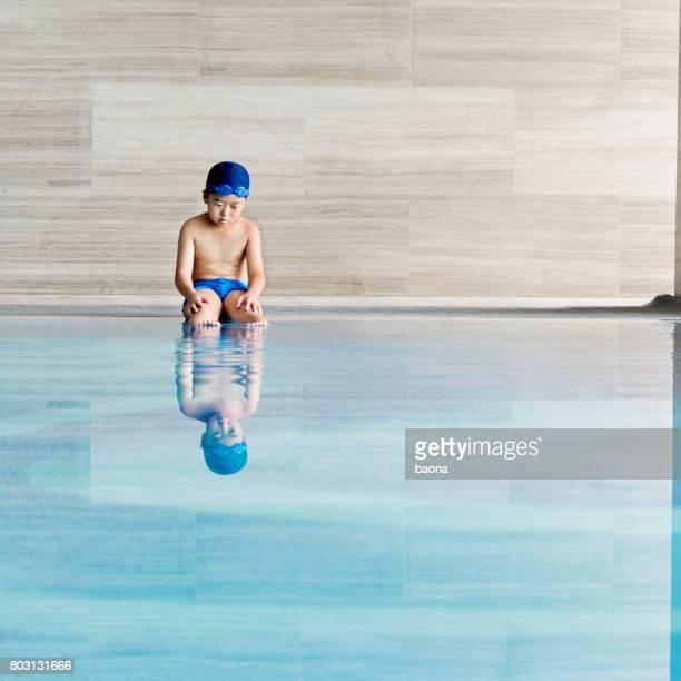 kleiner junge sitzt pool - knaben in badehosen stock-fotos und bilder