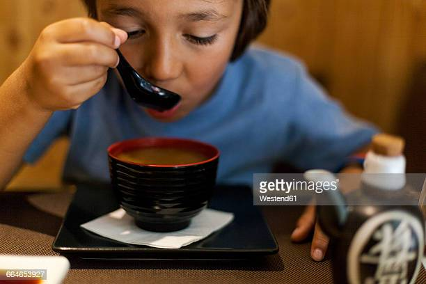 Little boy sitting in an Asian restaurant eating hot miso soup