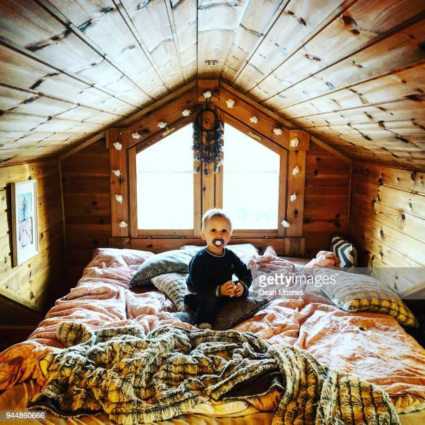 Little boy sitting on a bed in wooden house