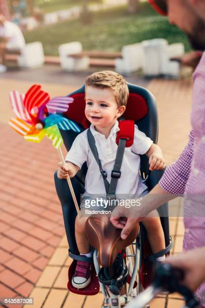 Little boy sitting on a child seat attached to a bicycle