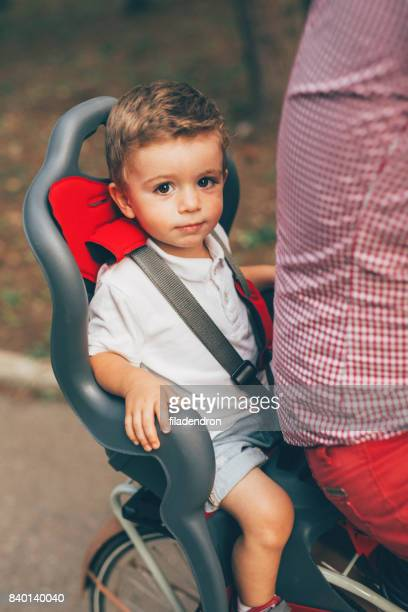Little boy sitting on a child seat on a bicycle