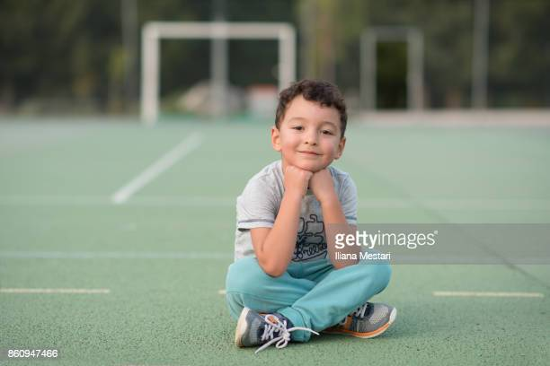 A little boy sitting on a soccer playground