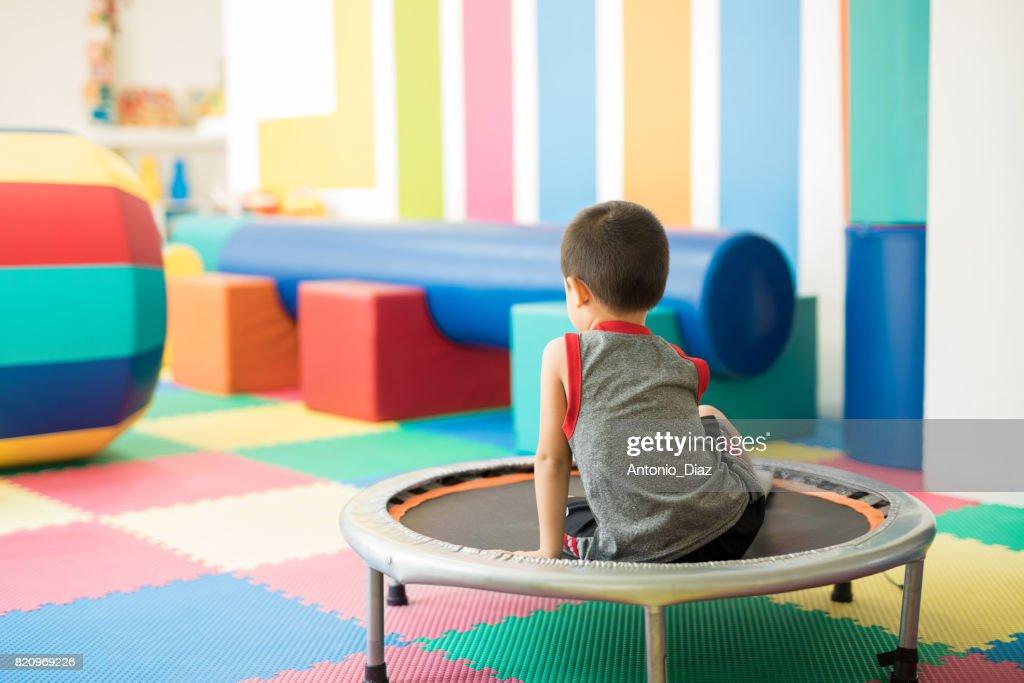 Little boy sitting on a trampoline : Stock Photo