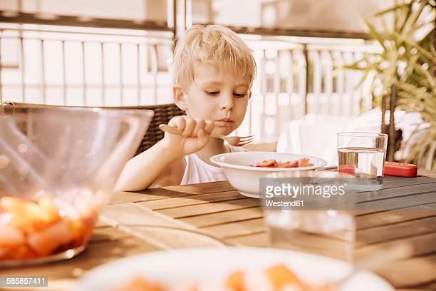 Little boy sitting on balcony eating fruit salad