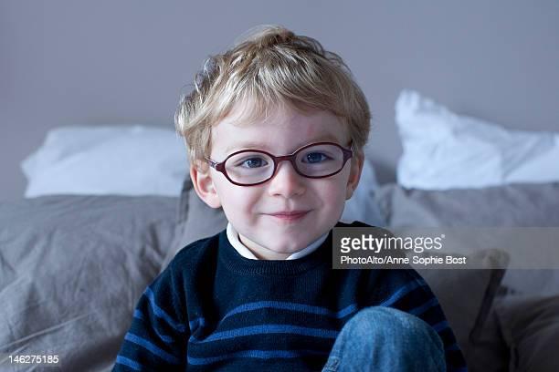 Little boy sitting on bed, portrait
