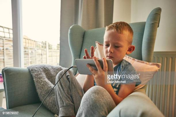 Little boy sitting on chair using mobile phone