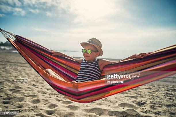 little boy sitting on hammock on beach - hammock stock pictures, royalty-free photos & images