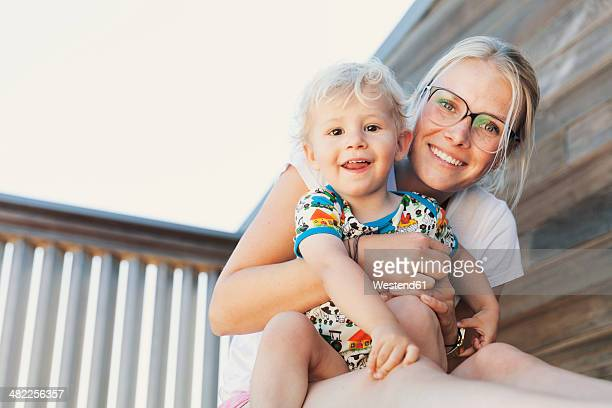 little boy sitting on his mothers lap - mom sits on sons lap stock pictures, royalty-free photos & images