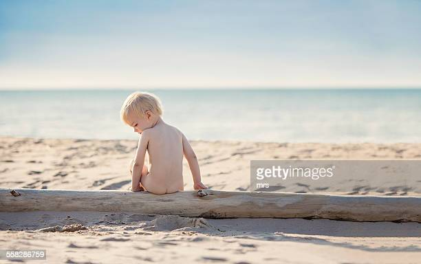 Little boy Sitting On Log At Beach