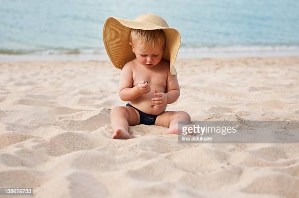 Little boy sitting on sand