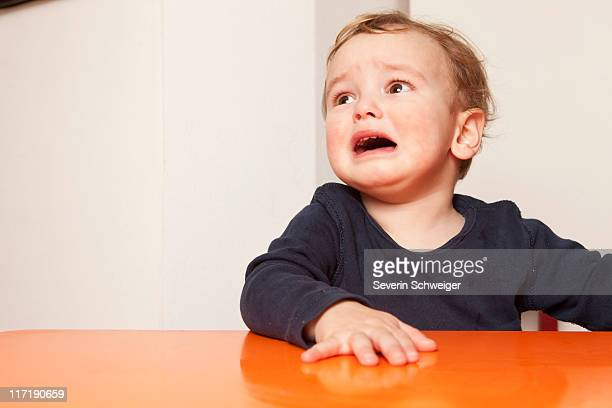 Little boy sitting on table crying