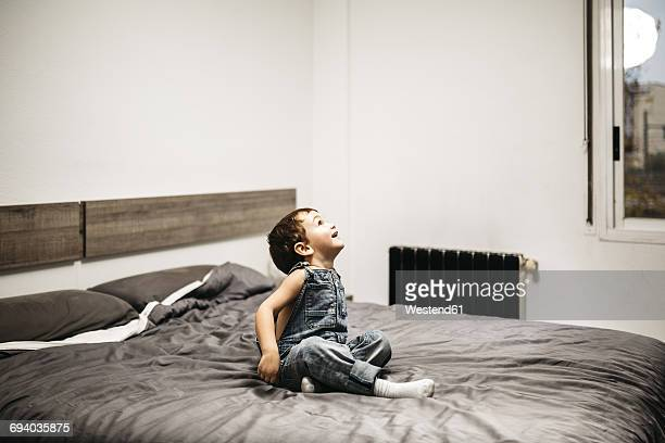 Little boy sitting on the bed of his parents watching something