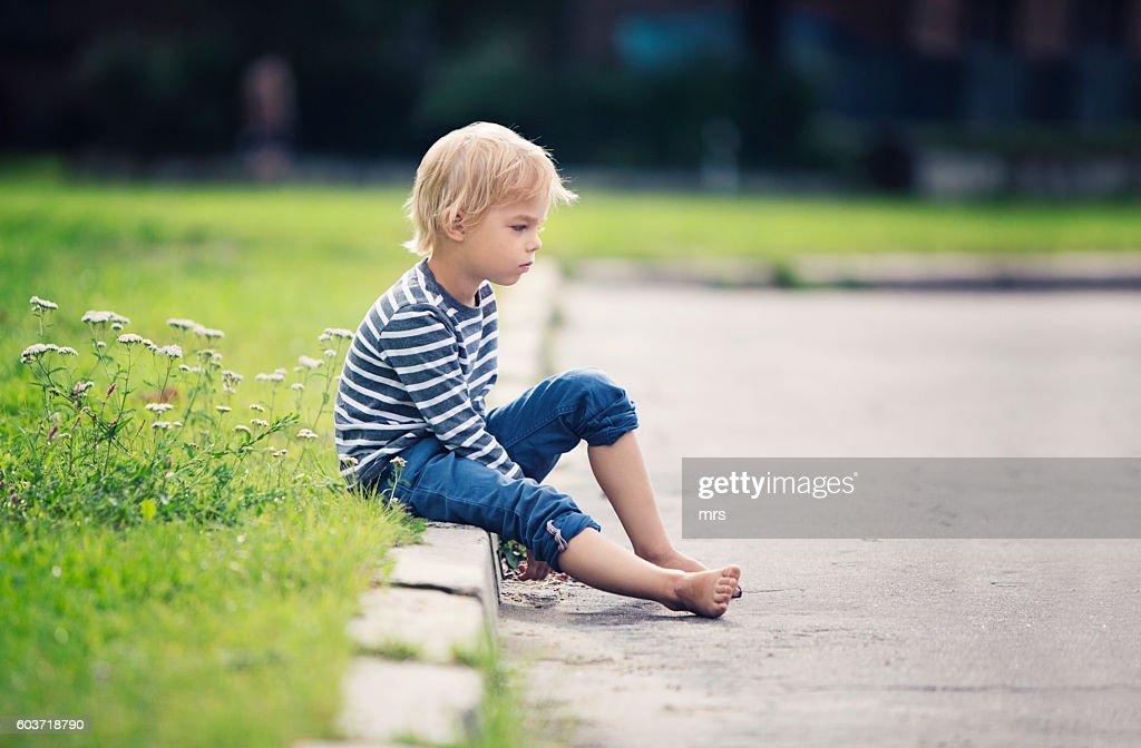Little boy sitting on the sidewalk : Stock Photo
