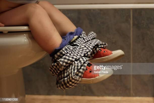 little boy sitting on toilet bowl in bathroom. potty training. - human toilet stock-fotos und bilder