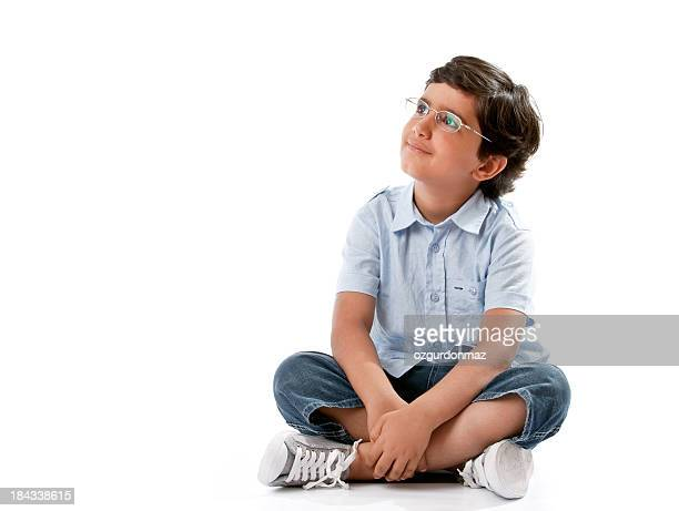 Little boy sitting on white