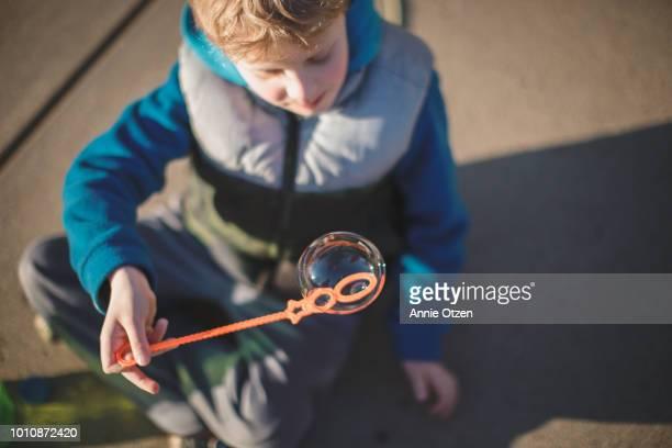 Little Boy Sitting outside with bubble