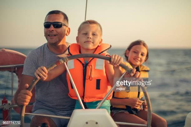 kleine jongen zitten met vader en stuurinrichting met zeilboot - zeilboot stockfoto's en -beelden