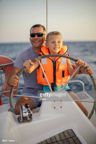 little boy sitting with father and steering with sailboat - thasos stock photos and pictures