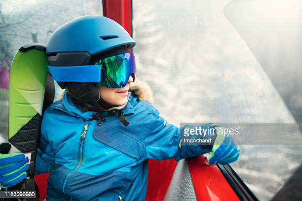 little boy skier in gondola ski lift - winter sport stock pictures, royalty-free photos & images