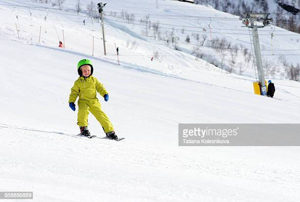 Little boy skiing down a snow slope by himself