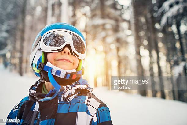 Little boy skiing in snowy forest on sunny winter day