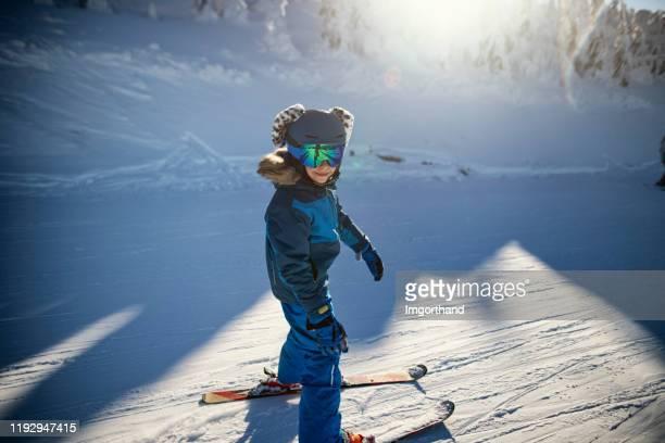 kleine jongen skiën op een mooie winterdag - alleen jongens stockfoto's en -beelden
