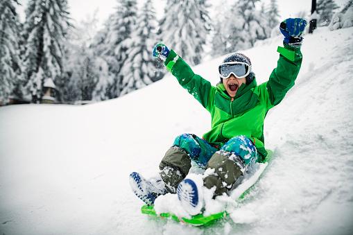 Little boy sledding and shouting 1068501818